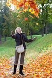 The beautiful woman throws up red maple leaves in a sunny day Royalty Free Stock Photos