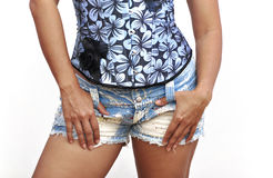 Woman thumbs in belt loops of mini denim shorts. Beautiful isolated woman sexy blue overbust with thumb in belt loop of daisy dukes Royalty Free Stock Images