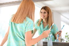 Beautiful woman with toothbrush near mirror in bathroom. Personal hygiene royalty free stock image