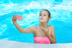 Beautiful woman tossing a kiss while talking on the phone Royalty Free Stock Photography