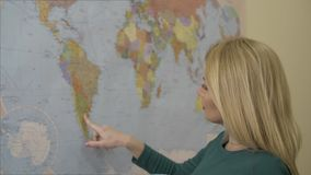 Beautiful woman touching finger world map on wall and dreaming about traveling. Portrait blond woman looking at world map in travel company office stock footage