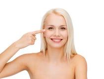 Beautiful woman touching her eye area Stock Photo