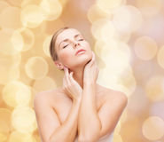 Beautiful woman touching her face with closed eyes Royalty Free Stock Photos