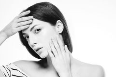 Beautiful woman touching her face by fingers close up portrait black and white Stock Photography