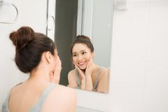 Beautiful woman touching her face by hands in her bathroom.  Stock Photos