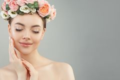 Beautiful woman touching her face her hand. Pretty candid girl with flowers. Facial treatment, face lifting, anti aging stock images