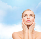Beautiful woman touching her face and looking up Royalty Free Stock Photo