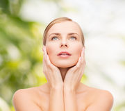 Beautiful woman touching her face and looking up Stock Images