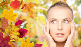 Beautiful woman touching her face over autumn Royalty Free Stock Image