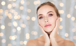 Beautiful woman touching her face over lights Royalty Free Stock Image