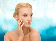 Beautiful woman touching her face skin Stock Photography