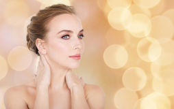 Beautiful woman touching her neck over lights Stock Images