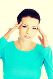 Beautiful woman is touching her temples. Royalty Free Stock Photos