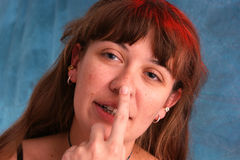 Beautiful woman touching nose. A beautiful woman is touching her nose as if taking sobriety test, shot with red and blue strobes to enhance colors Stock Photography