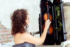 Beautiful woman touching violin Royalty Free Stock Photography