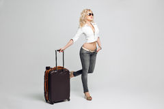 Beautiful woman tourist going on vacation, a suitcase full of things, wearing a leather jacket and gray jeans, high Stock Photos