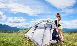 Woman tourist hiking in mountain trail, enjoying summer sunny morning in mountains near tent royalty free stock images