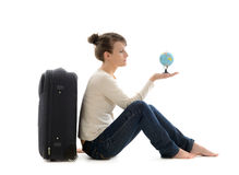 Beautiful woman tourist with suitcase and globe. Holidays and tourism concept. Portrait of beautiful european woman tourist sitting with suitcase and little Stock Photography