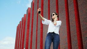 Beautiful woman tourist uses a mobile phone for video call to friends near a modern brick building, exhibition center stock video footage