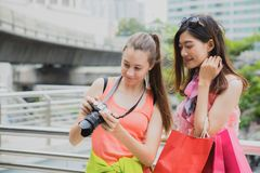 Beautiful woman tourists looking photo in her camera after travel and shopping in the city downtown. royalty free stock image