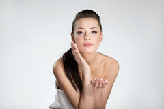Beautiful woman in towel applying cream on face Stock Image