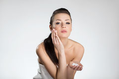 Beautiful woman in towel applying face cream Royalty Free Stock Image