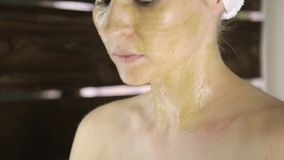 Beautiful woman in towel applying green clay mud mask to her face. Skin care and home Spa