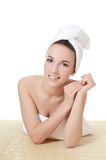 The beautiful woman in a towel on bamboo rug Royalty Free Stock Photo