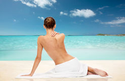 Beautiful woman in towel with bare top on beach Stock Photography