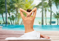 Beautiful woman in towel with bare top on beach. Beauty, people and bodycare concept - beautiful young woman in white towel with bare top over beach and outdoor Royalty Free Stock Photos