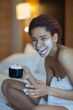 Beautiful woman in towel on the bed drinking coffee with whipped cream stock photography