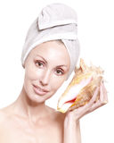 The beautiful woman with a towel on the head and a big sea cockleshell Stock Photography
