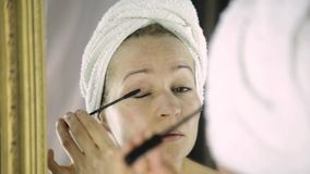 Beautiful woman in towel paints eyelashes in front of mirror stock video