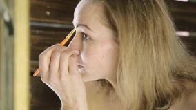Beautiful woman in towel, paints her eyebrows in front of mirror stock video footage