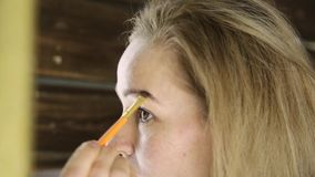Beautiful woman in towel, paints her eyebrows in front of mirror stock footage