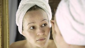 Beautiful woman in towel plucking her eyebrows. Skin care and home Spa stock footage