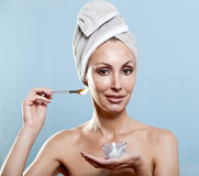 The beautiful woman in a towel puts cream Stock Images