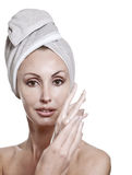 The beautiful woman in a towel puts cream Royalty Free Stock Image