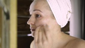 Beautiful woman in a towel takes off makeup in front of the mirror. Spa at home stock video footage