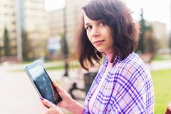 Beautiful woman in town using electronic tablet Stock Photography