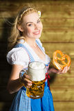 Beautiful woman in a traditional bavarian dirndl with beer and pretzel Royalty Free Stock Image