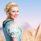 Beautiful woman in traditional bavarian dirndl. Beautiful woman in a traditional bavarian dirndl in front of a crop field stock photography