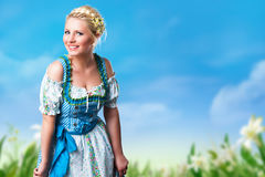 Beautiful woman in a traditional bavarian dirndl. In front of flower field royalty free stock photography