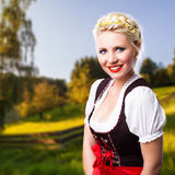 Beautiful woman in a traditional bavarian dirndl. In front of a green meadow stock photos