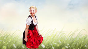 Beautiful woman in traditional bavarian dirndl. Beautiful woman in a traditional bavarian dirndl in front of a meadow stock photography