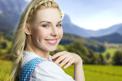 Beautiful woman in a traditional bavarian dirndl. In front of bavarian mountainscape stock photo