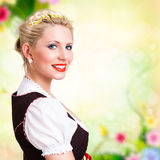 Beautiful woman in traditional bavarian dirndl. Beautiful woman in a traditional bavarian dirndl in front of spring scene royalty free stock photography