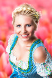 Beautiful woman in a traditional bavarian dirndl. In front of tulip field royalty free stock photos
