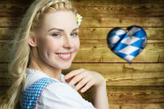 Beautiful woman in a traditional bavarian dirndl. In front of wooden background royalty free stock photography