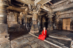 Beautiful woman in traditional indian dress sitting on stone floor of 12th century temple Hoysaleswara, India. Royalty Free Stock Image